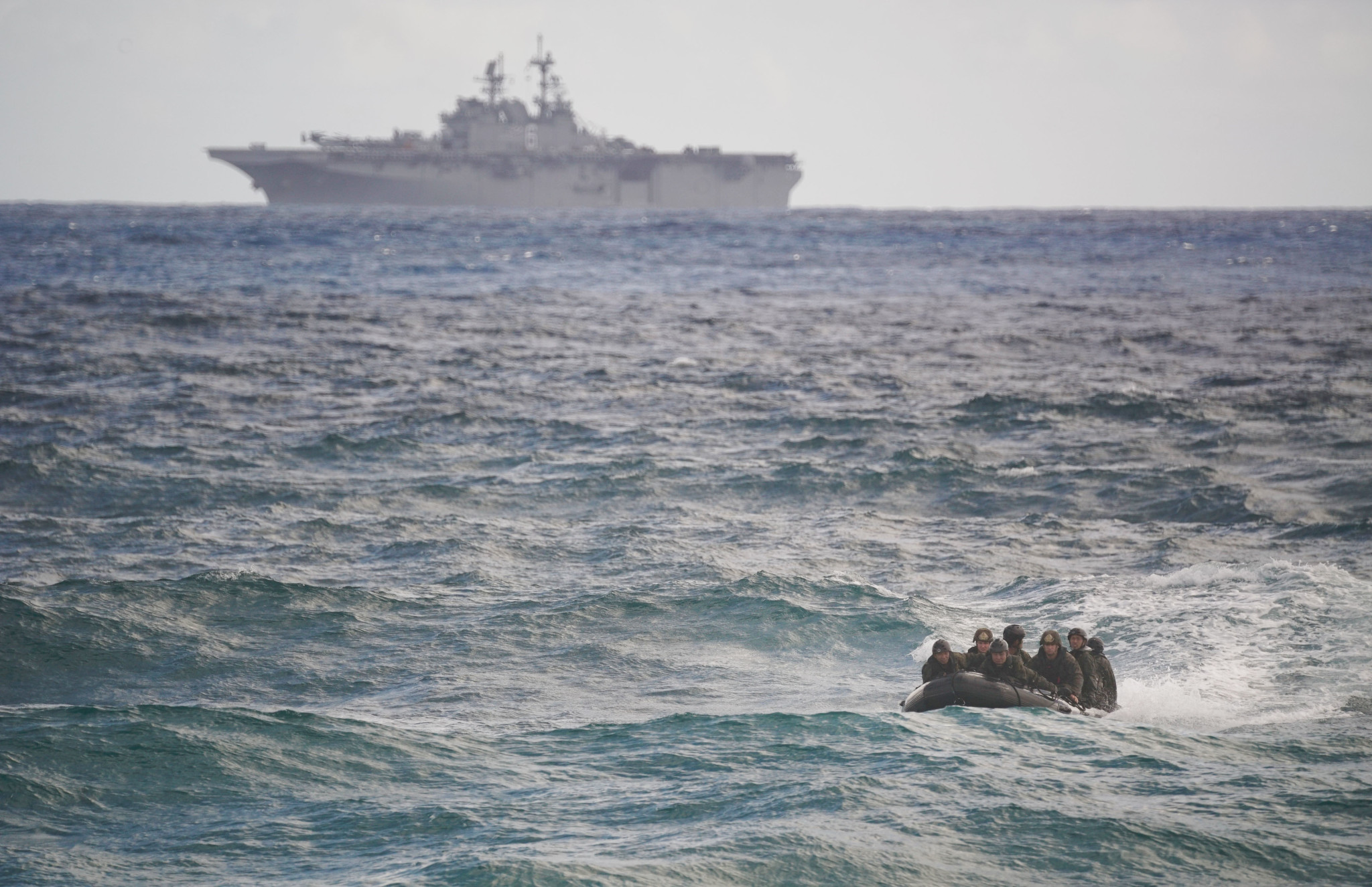 <p>With the USS America amphibious assault ship in the background, a reconnaissance team approached the beach in an inflatable raft.</p>