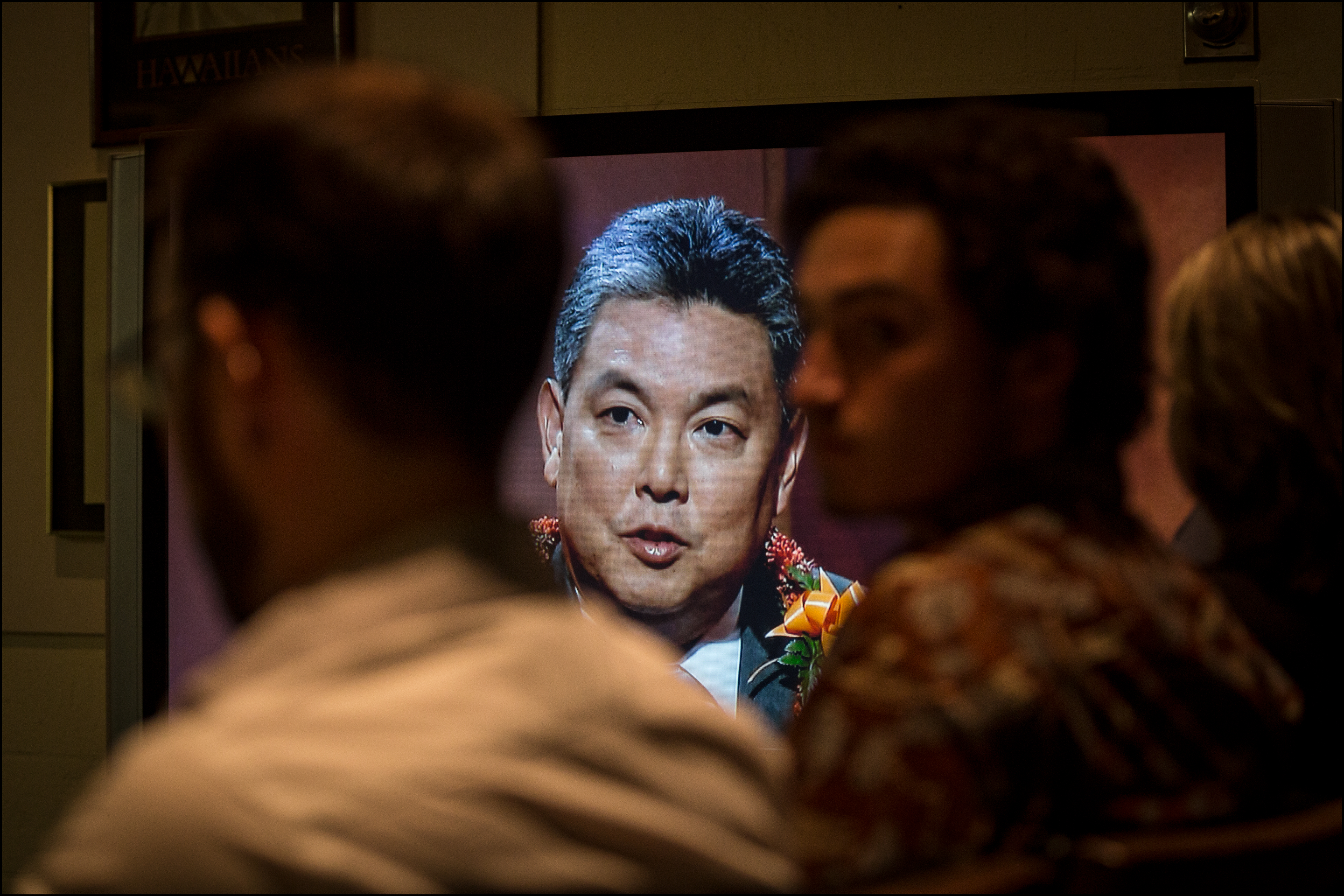 <p><strong>July 2014, Primary Battle:</strong> During the eight-candidate contest for the Democratic nomination for urban Oahu's 1st Congressional District, campaign staffers and reporters watch Mark Takai on a TV screen. (Civil Beat photo by PF Bentley)</p>
