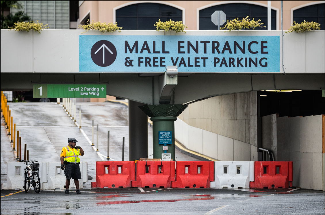 Amid concern that the storm would worsen a security guard made sure that no one came to Ala Moana Shopping Center, which was closed. But in the end, Honolulu endured very little damage and only a moderate tropical storm. (Cory Lum, special for Civil Beat)