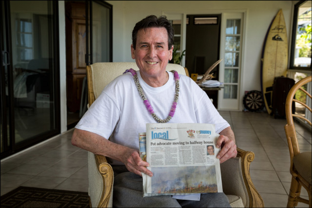Cannabis advocate Roger Christie holds up Star-Advertiser story as he sits in candidate for governor Jeff Davis' home on the way to Mahoney Hale, a halfway house in downtown Honolulu. on September 11, 2014
