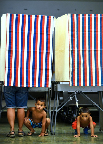 Right, 3-year-old Lucan Keawe-Kekoa plays with left, brother 5-year-old Aliiokekai Keawe-Kekoa while mom, Cassandra Kekoa casts her vote at Nanaikapono Elementary School located at 89-153 Mano Avenue in Waianae, Hawaii. 4 November 2014. photography by Cory Lum