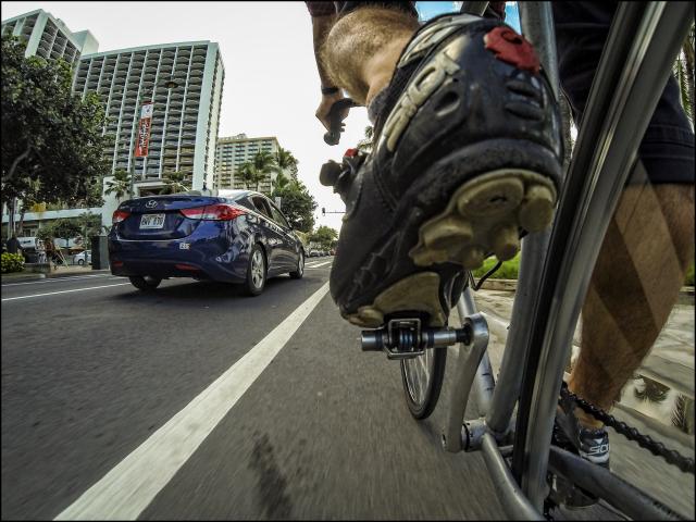 Bicyclist shares road with cars along Kalakaua Ave in Waikiki. 3.6.14 ©PF Bentley/Civil Beat
