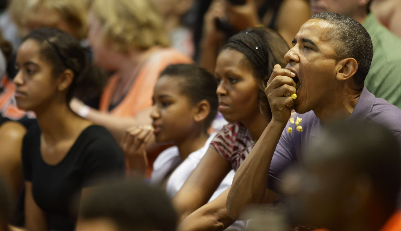 <p>The president loses a few kernels of popcorn as he watches a basketball game in December 2013 at the Stan Sheriff Center with his family, from left, Malia, Sasha and Michelle. They&#8217;re watching the team from Oregon State, then coached by the first lady&#8217;s brother, Craig Robinson.</p>
