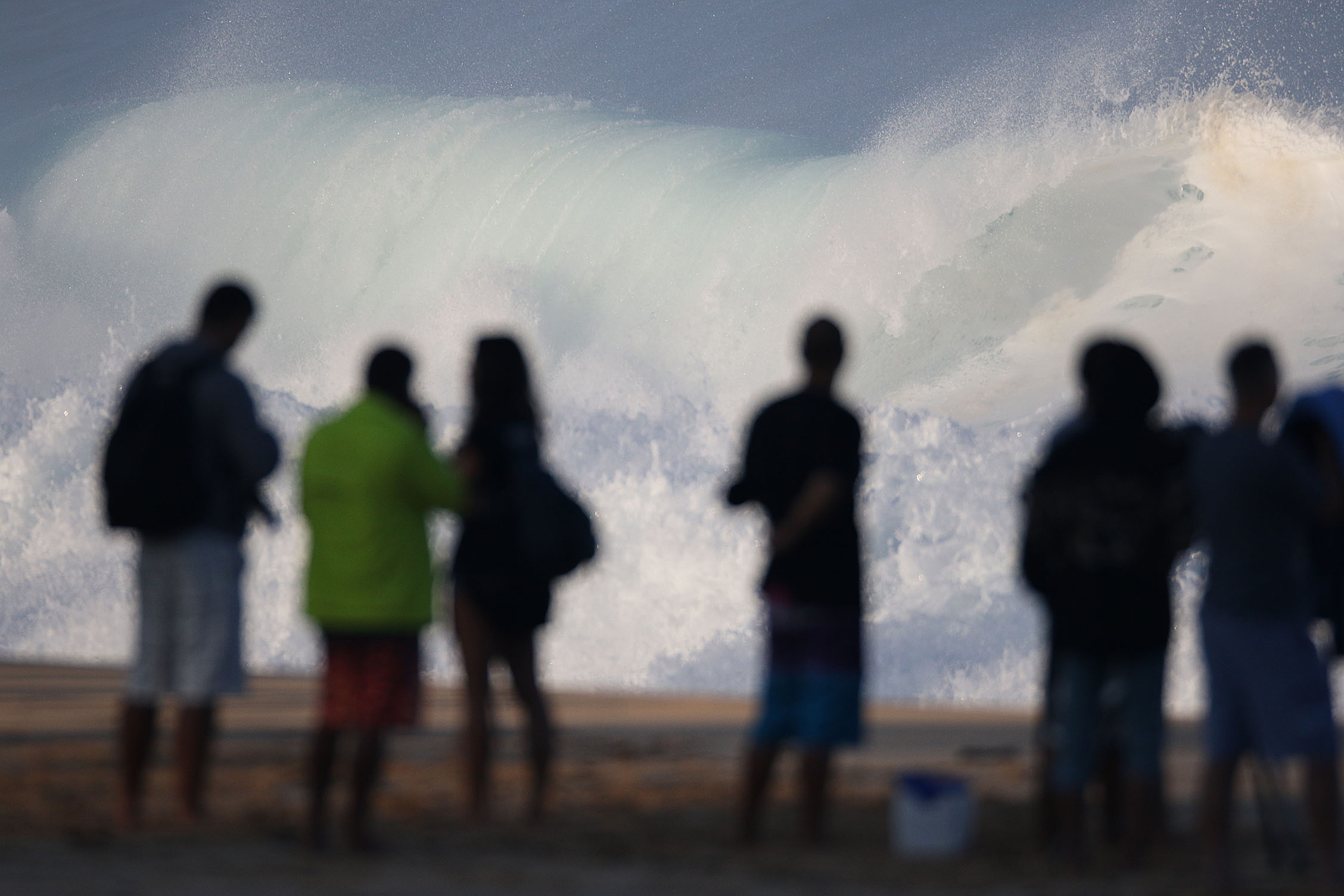 <p>Beachgoers watch the large surf at the Banzai Pipeline. Winter waves are sometimes so epic you'd think the hazards are obvious, but lifeguards issue plenty of warnings anyway.</p>