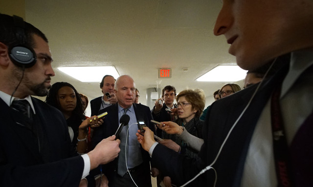 Senator John McCain is mobbed by journalists in the basement on his way up to cast his vote in the Senate Chamber. 23 feb 2015. photograph Cory Lum/CIvil Beat