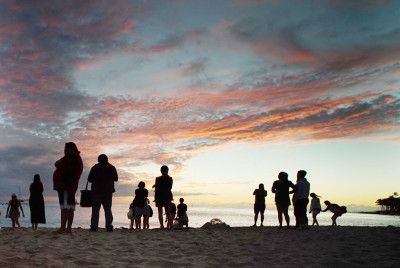 Visitors to Waikiki Beach fronting the Moana Sheraton enjoy crimson sunset. 8 march 2015. photograph Cory Lum/Civil Beat
