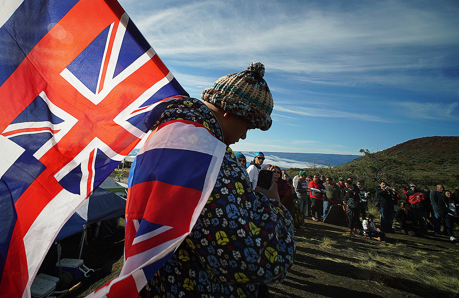 Big Island resident Kalae Kauwe is draped in Hawaiian flags as hula halau dance near the Mauna Kea visitors center.