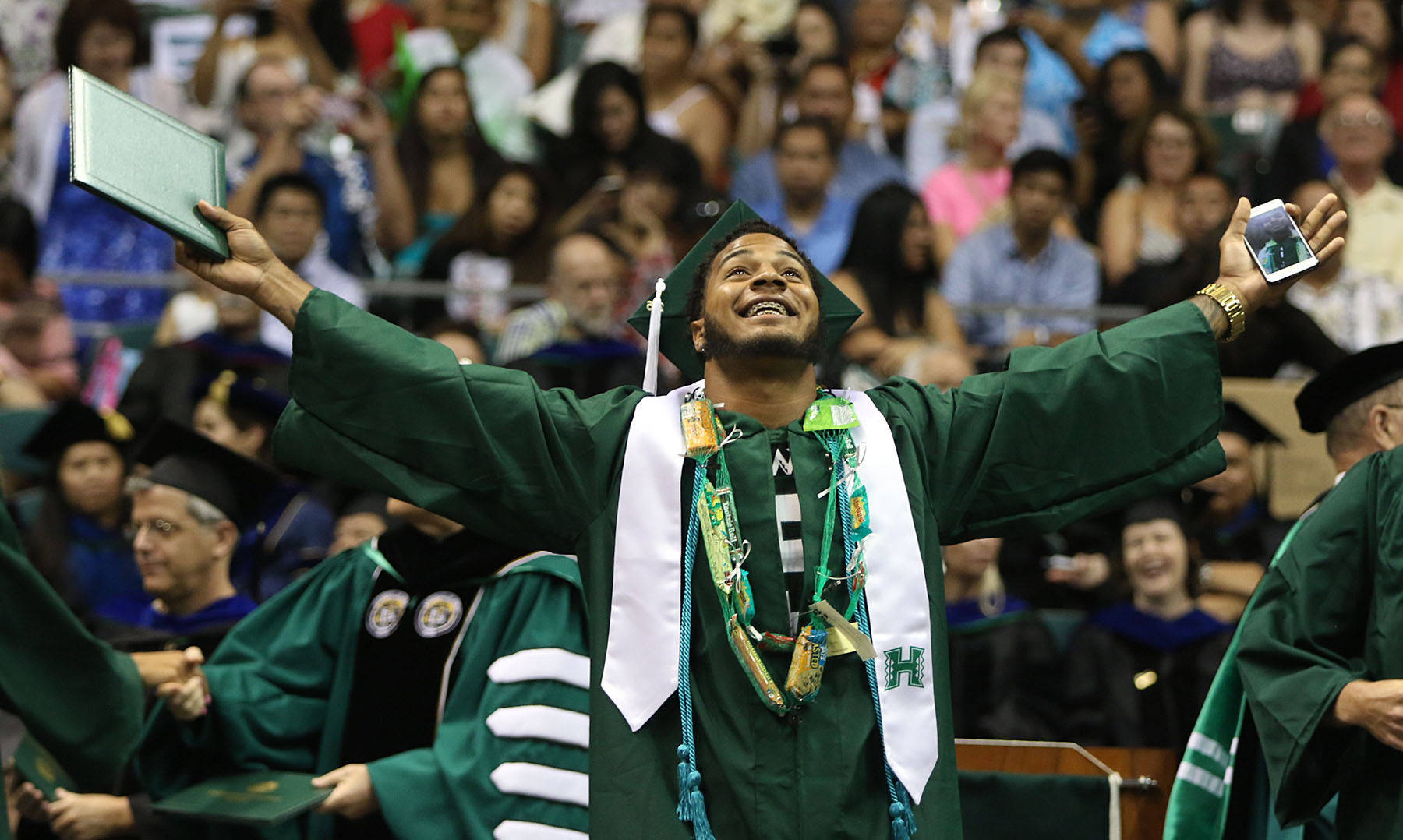 <p>Quinton Pedroza celebrates after receiving his degree during the University of Hawaii commencement in mid-May at the Stan Sheriff Center.</p>