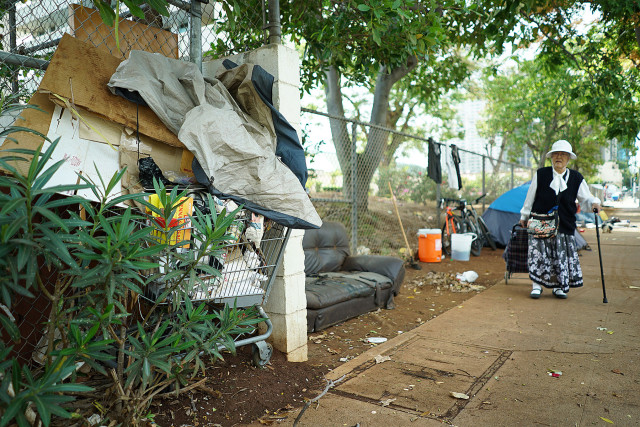 An elderly woman walks past tents located along Beretania Street across from Aala Park with tents and a shopping cart full of garbage. 4 june 2015. photograph Cory Lum/Civil Beat