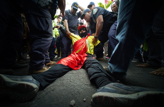 TMT demonstrator lays on the ground refusing to move out of the DLNR motorcades movement up the Maunkea Observatory access road as hundreds of anti TMT and protect Maunakea demonstrators slowed the movement of the DLNR motorcade from the Maunakea Visitors Center. 24 june 2015. photograph Cory Lum/Civil Beat