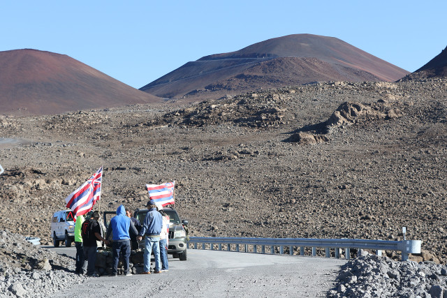 Supporters of Maunakea stand near a stone altar or 'ahu' along the Maunakea summit access road. 24 june 2015. photograph Cory Lum/Civil Beat