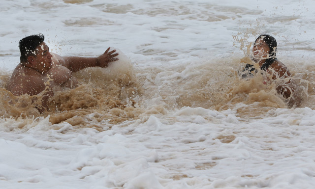 Two folks after being warned by lifeguards about large waves and shorebreak get inundated by a set while not watching the waves at Sandy Beach. 9 july 2015. photograph Cory Lum/Civil Beat