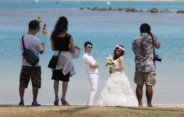 Married couples pose for photographs along the Magic Island side of Ala Moana Beach Park. Mayor Caldwell held a press conference outlining updates to the Ala Moana Beach Master plan. 15 july 2015. photograph Cory Lum/Civil Beat