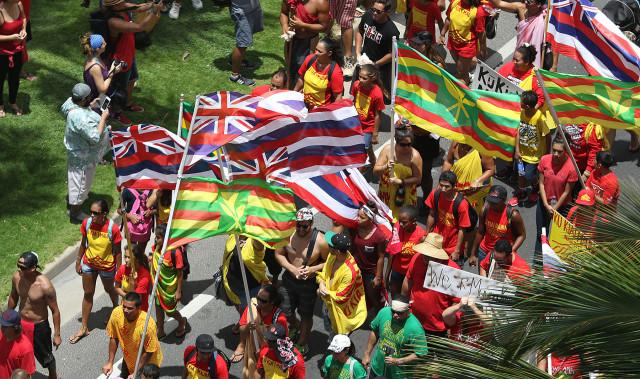 Flag waving Aloha Aina Unity Demonstrators walk along Kalakaua Avenue on their way to Kapiolani Park for a rally. 9 aug 2015. photograph by Cory Lum/Civil Beat