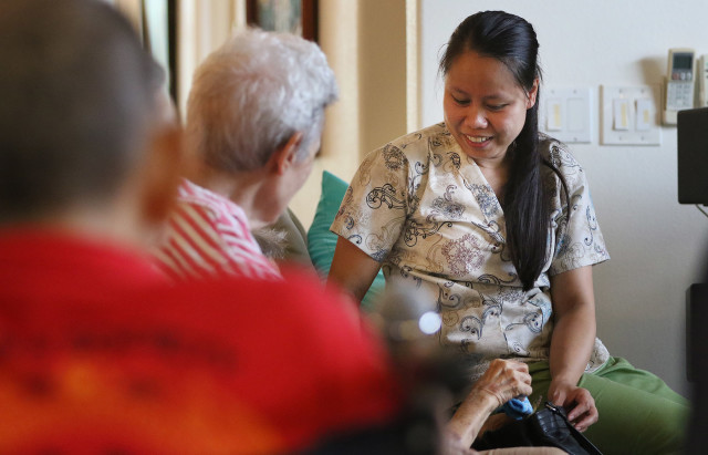 CNA Juvy Requilman talks to residents at Hokulaki Senior Living care home in Kaneohe. 14 aug 2015. photograph Cory Lum/Civil Beat