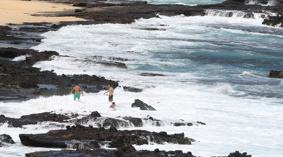 Stupid people play near breaking waves as Hurrican Ignacio skirts north of the Hawaiian islands. 31 aug 2015. photograph Cory Lum/Civil Beat