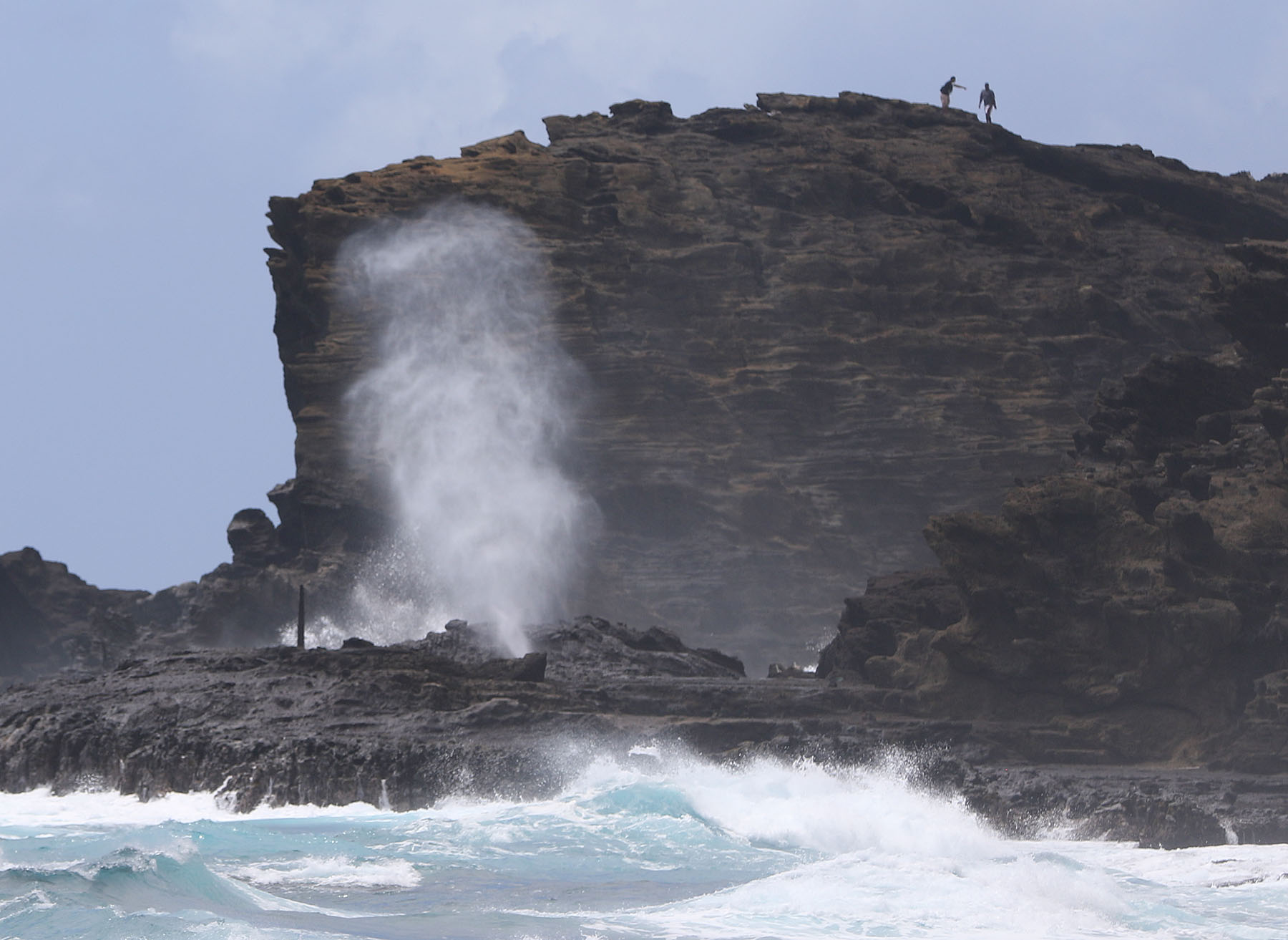 <p>Ignoring signs warning people to stay behind a fence, visitors climb the cliffs at Oahu&#8217;sHalona Blowhole.</p>