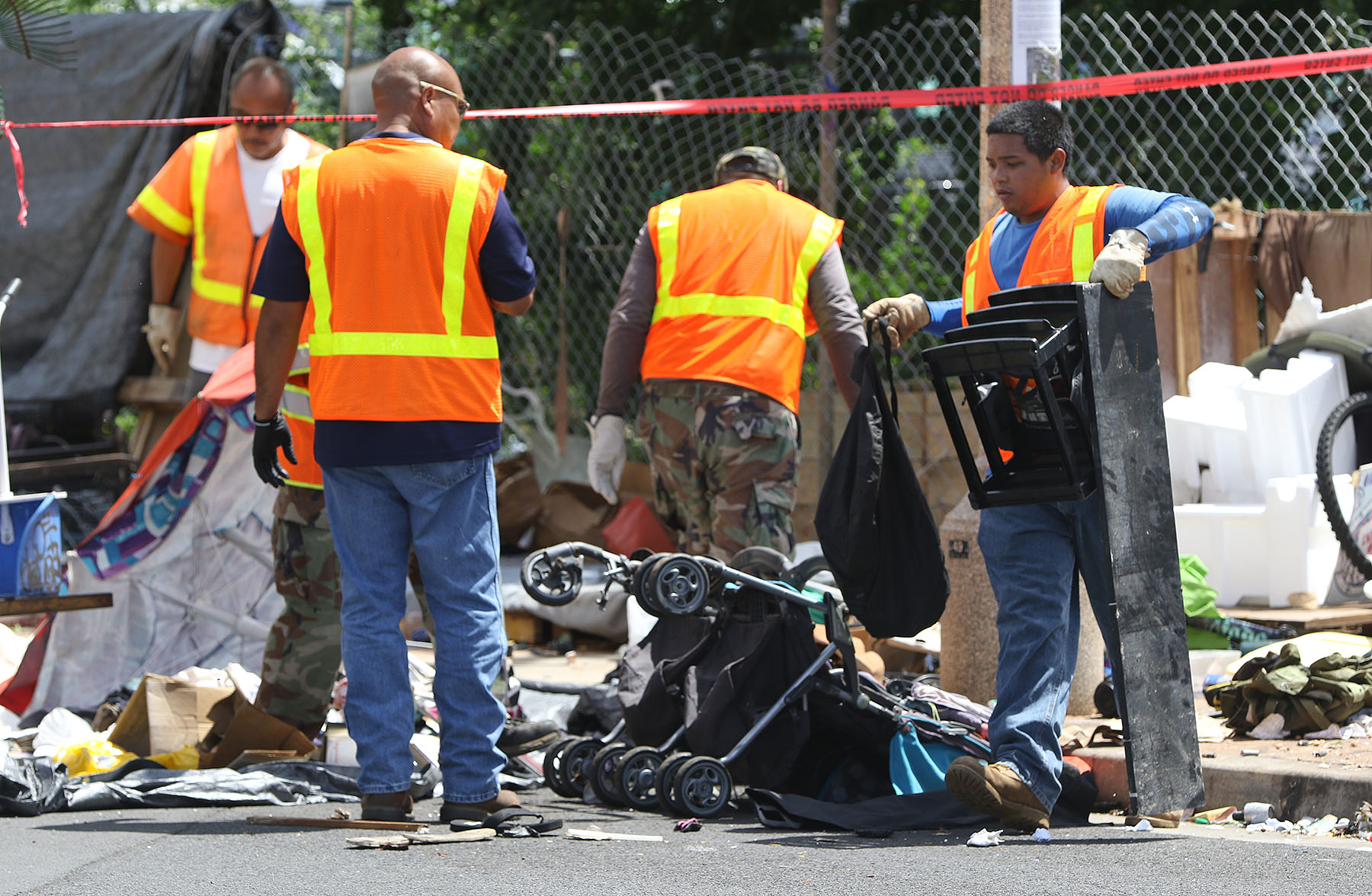 <p>A city maintenance crew sorts through trash and the possessions of the homeless near Keawe and Ilalo streets Monday during another sweep of a Kakaako homelessencampment. On Tuesday, a federal judge rejected a request for a temporary restraining order to stop the sweeps.</p>