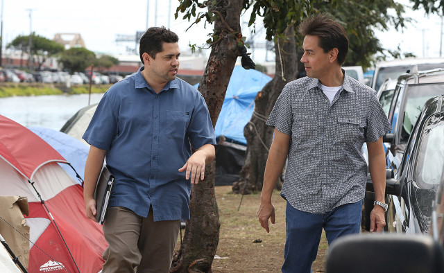 Kimo Carvalho of the Institute for Human Services, left, and Honolulu City Council member Joey Manahan tour the homeless camp along the Kapalama Canal in April.