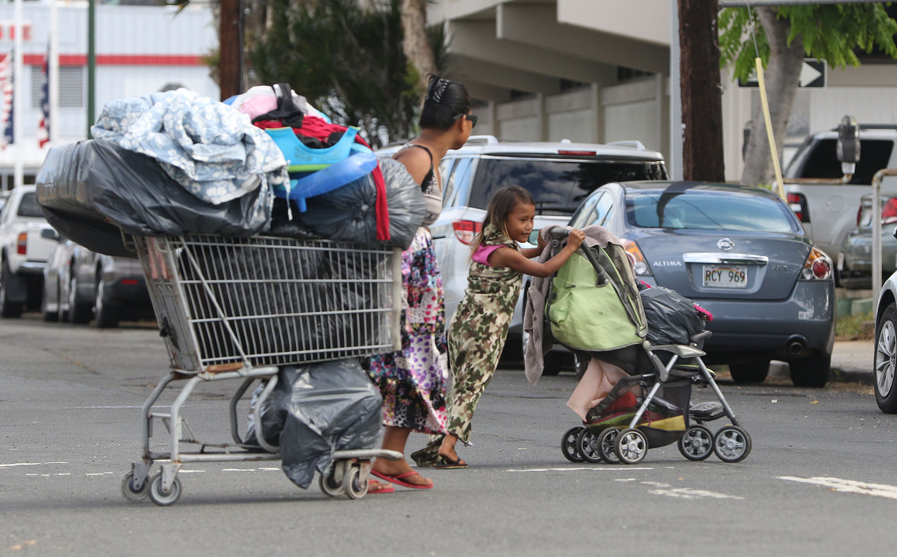 <p>A family on the move along Ahui Street during a city sweep in Kakaako in early October.</p>