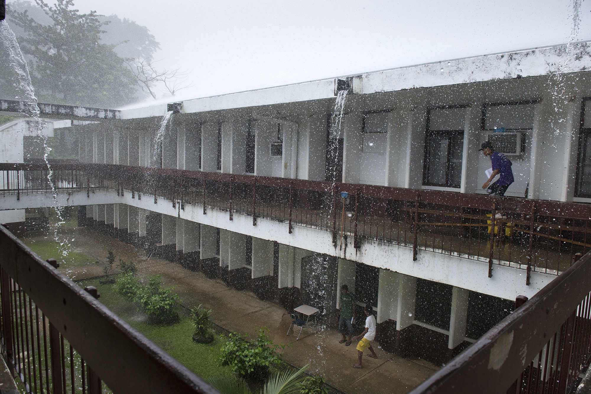 <p>A downpour at Chuuk High School. Because of little or no drainage, rain often leads to pooling on the streets.</p>