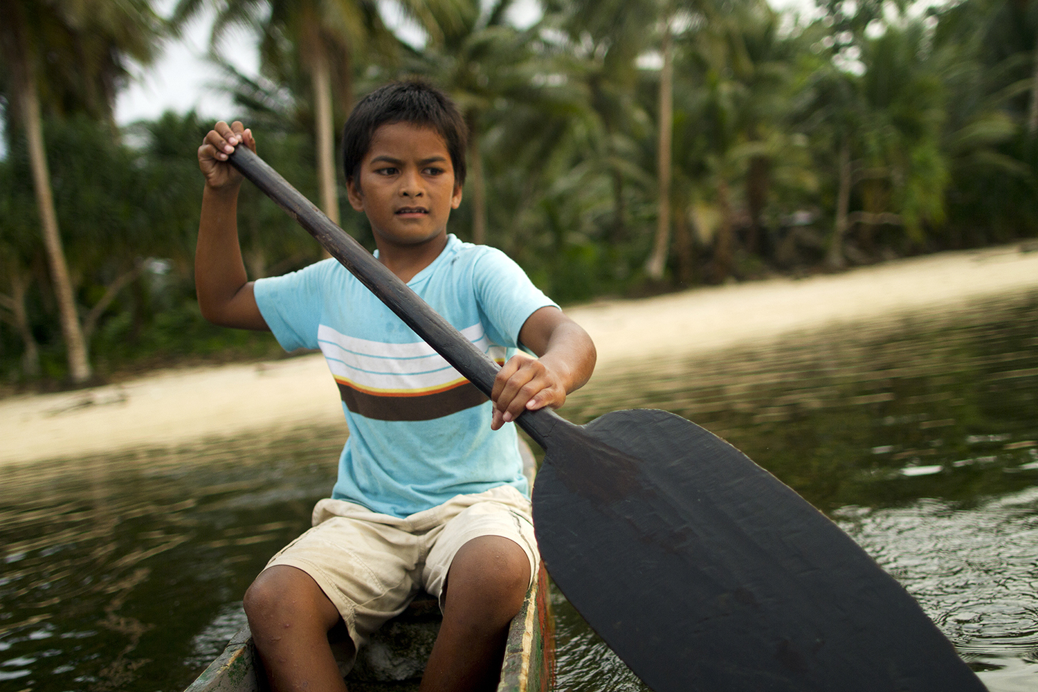 <p>A boy paddles home in Walung, Kosrae. Photo by Nathan Fitch.</p>