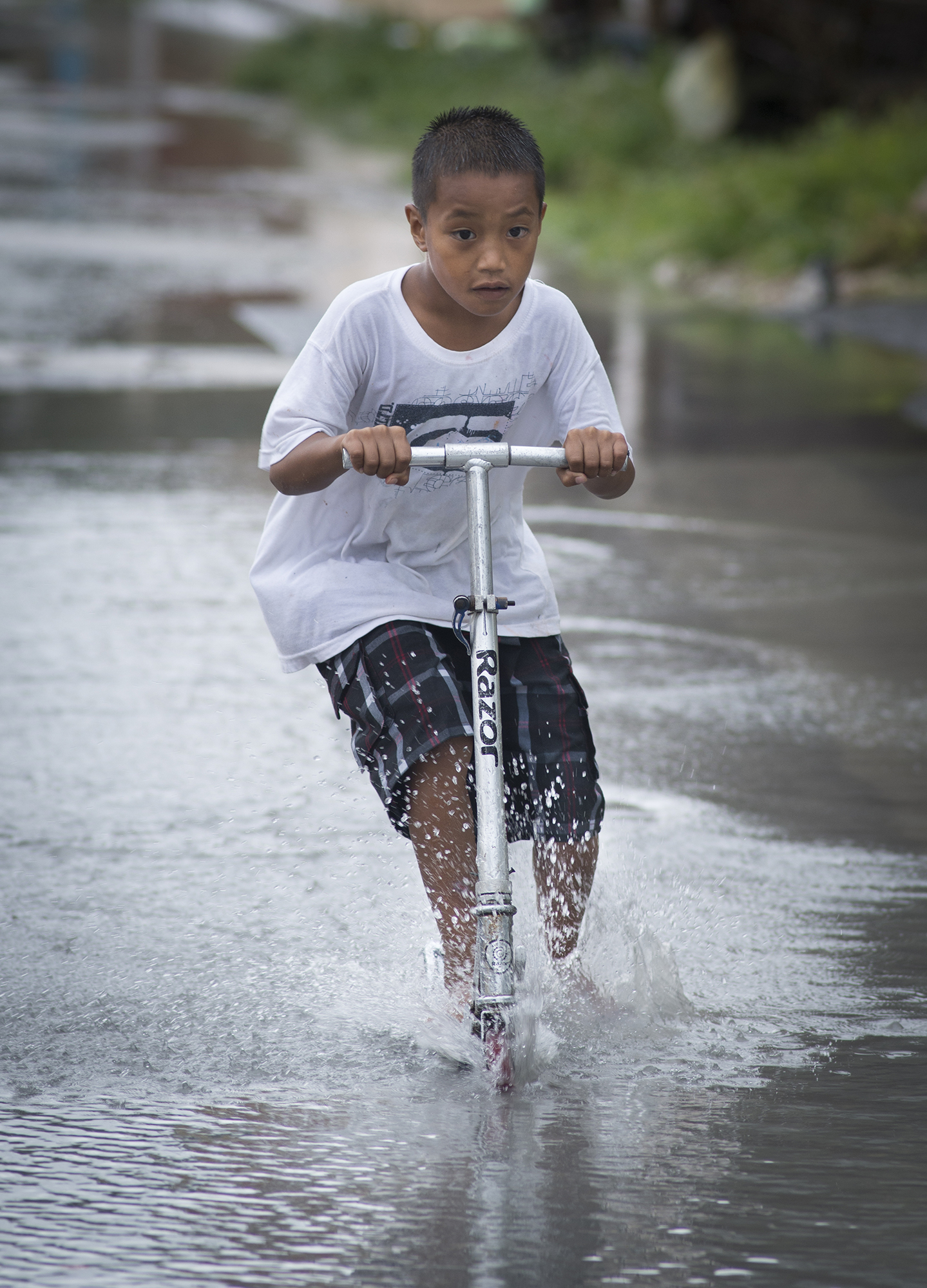 <p>A boy on his scooter on Ebeye. Parts of the Marshall Islands receive heavy rainfall.</p>