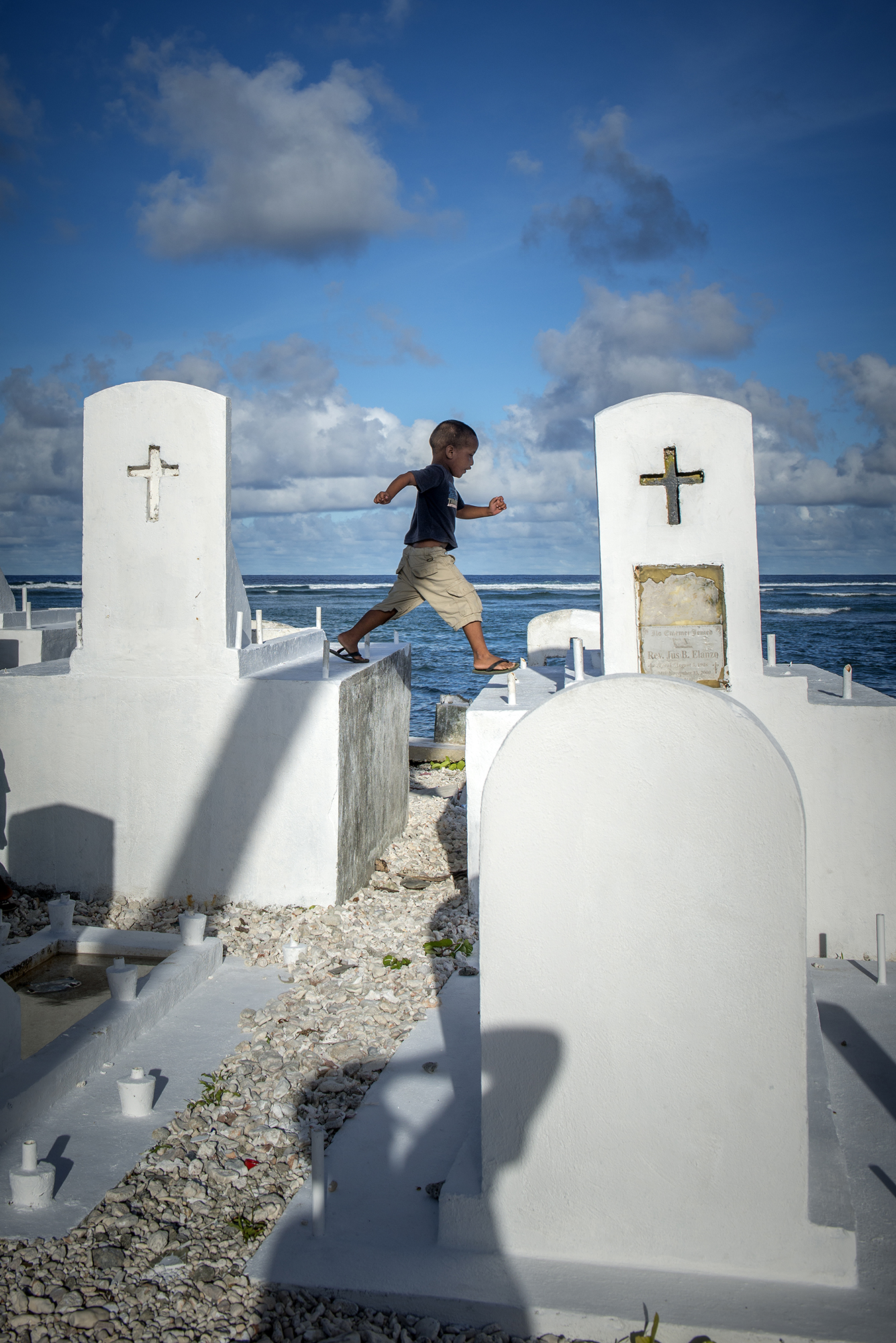 <p>A child plays in a cemetery that is gradually crumbling into the ocean as climate change raises the sea level. Photo by Mark Edward Harris.</p>