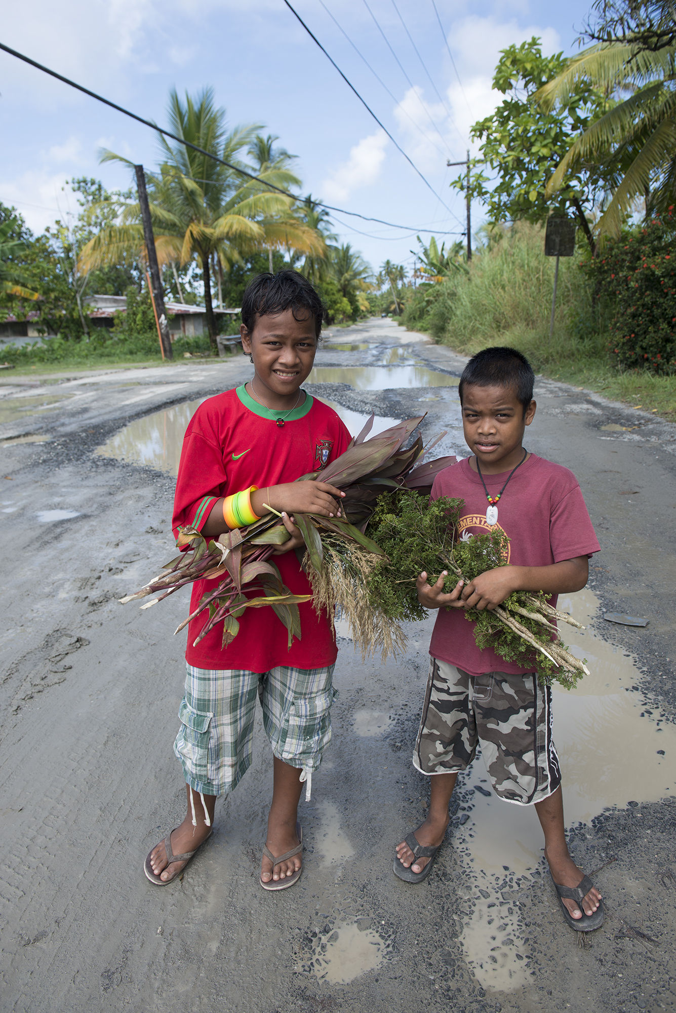 <p>Children play without care on Weno's main road, calling to passersby from America.</p>