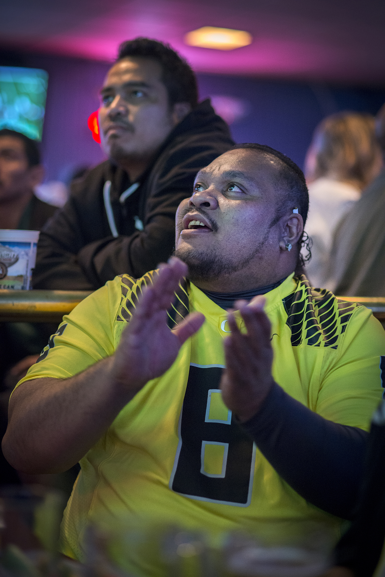 <p>Johnny Fred, foreground, and Dedao Yens, two immigrants from Pingelap Atoll in Pohnpei, cheer for the the Oregon Ducks at Pub 181 in Gresham during the college football national championship game.</p>