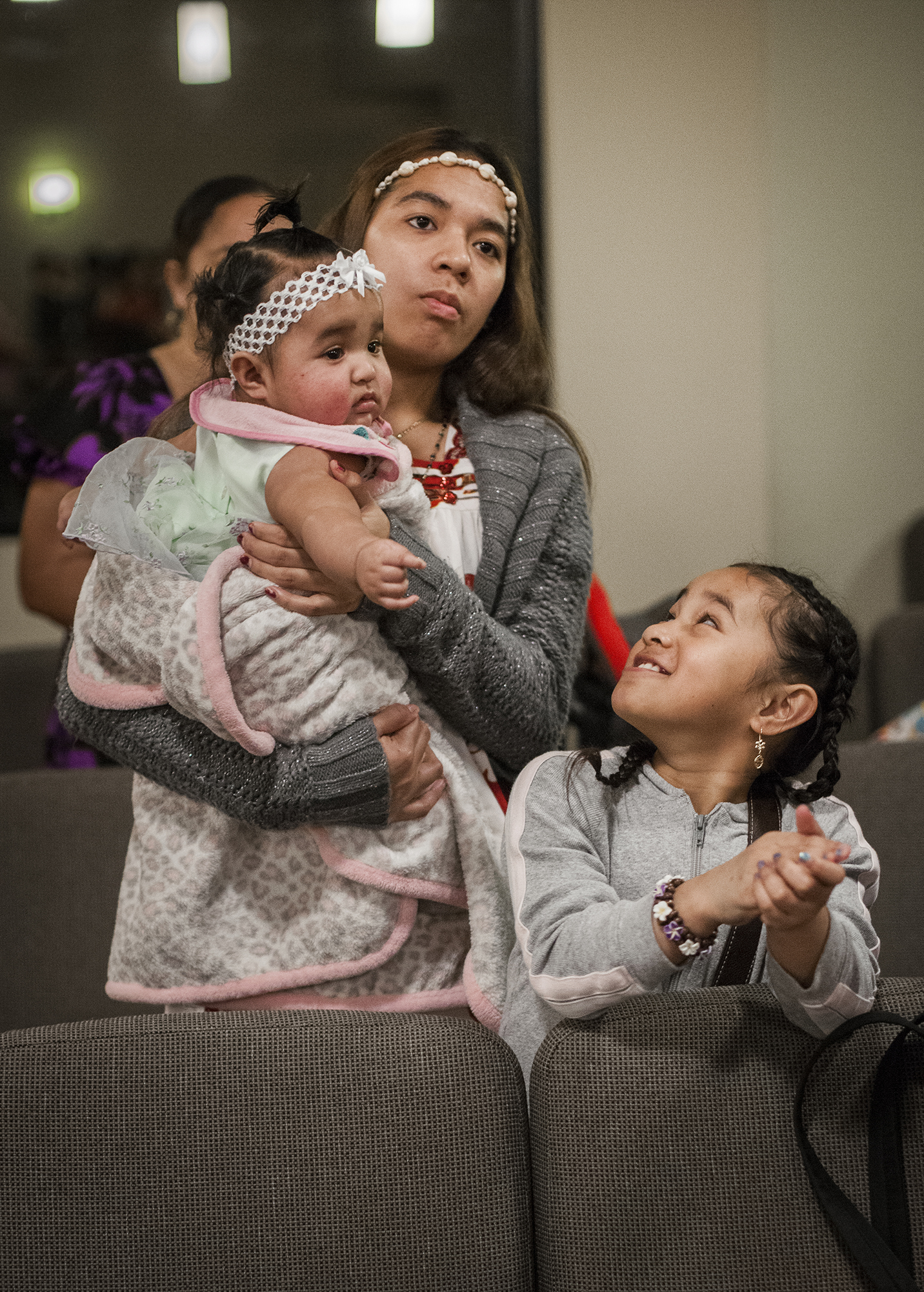 <p>A mother has her hands full during a Chuukese church service in Vancouver, Washington.</p>