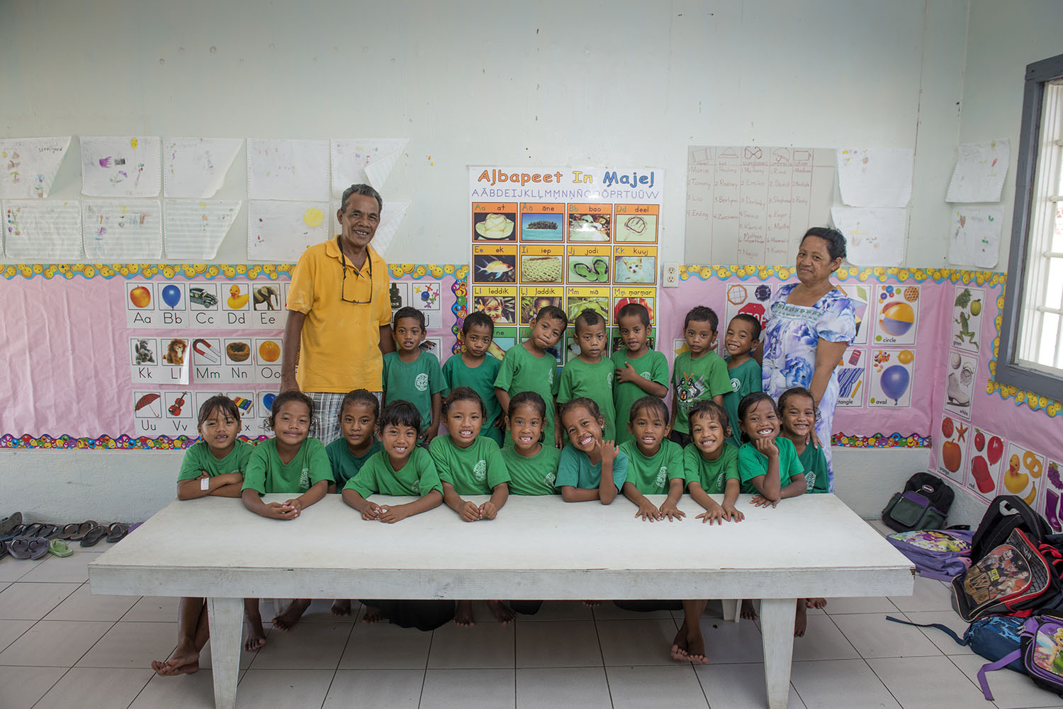 <p>Deonaire Keju, a vice principal at an Ebeye elementary and middle school, with a teacher and her class. Keju says his school hopes to expand access to the Internet, but government funding is limited.</p>