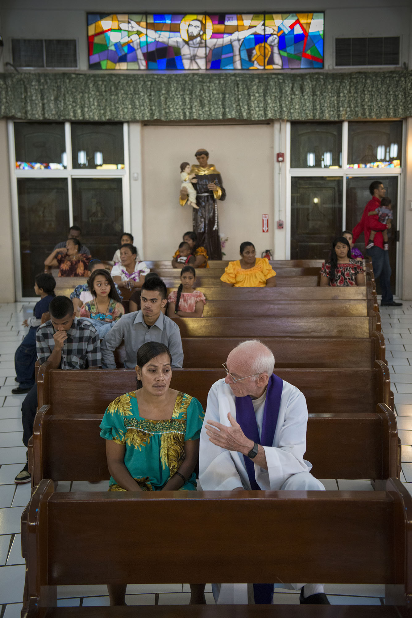 <p>Father Francis X. Hezel, right, takes confession at the Parish of Santa Barbara. Hezel has extensively studied the Micronesian culture and economy and written numerous books and papers on the region.</p>