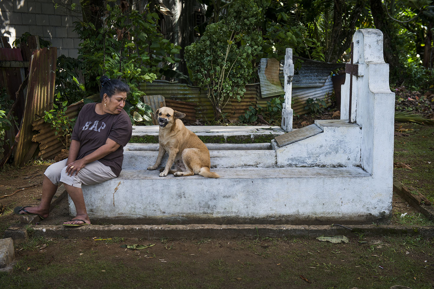 <p>A Pohnpei woman pauses for a few minutes with her dog at a cemetery on Pohnpei.</p>