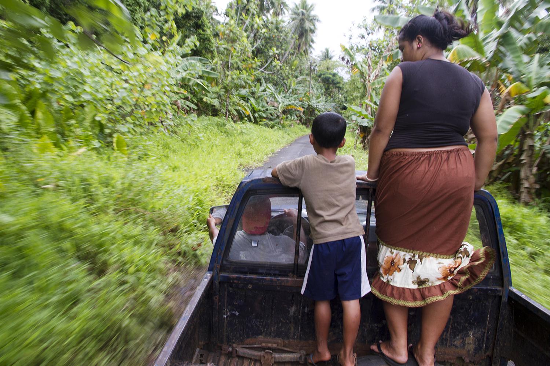 <p>Siblings ride on a flat bed truck in Nett.</p>