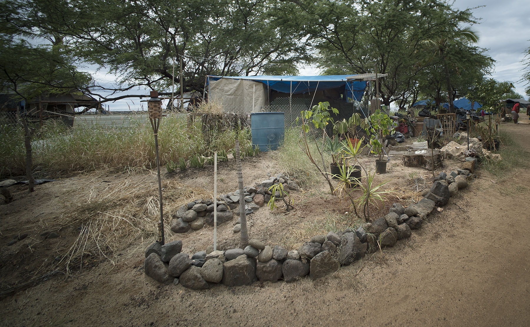<p>Tita landscaped the area around her tent with tiki torches and a small plastic tub that she hopes to turn into a solar-powered water fountain.</p>