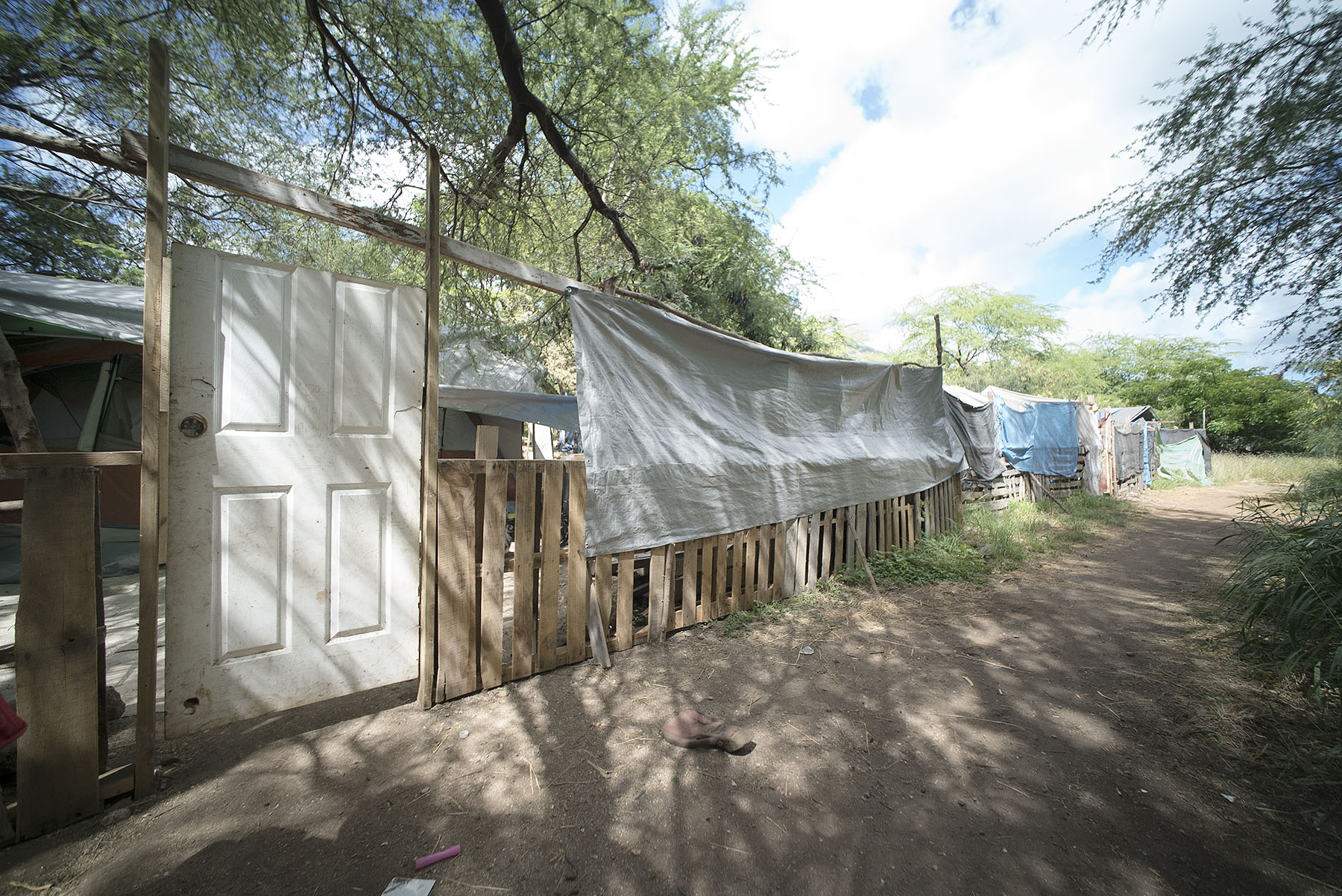 <p>In October one Micronesian family moved out of this gated site, and another family moved in. Behind the door is a large area with several tents and a giant carpet covering the ground.</p>