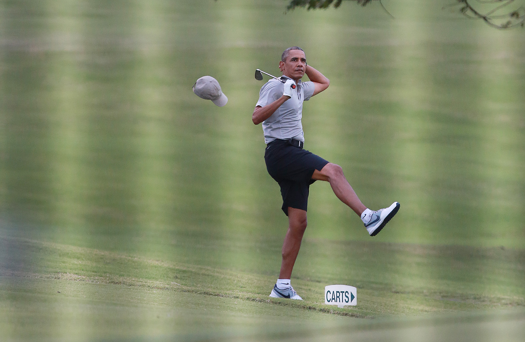 <p>In late December, the Obamas are back for another Hawaiian vacation. Viewed through a fence, President Obama loses his hat to the wind at the Mid Pacific Country Club in Kailua before recovering nicely to chip in a 40-foot shot on the 18th hole.</p>