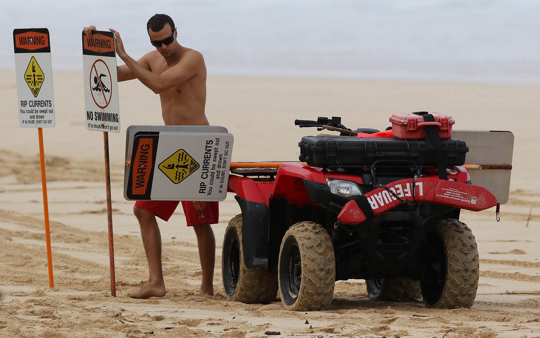 <p>A lifeguard places signs warning of rip currents and unsafe swimming at the Banzai Pipeline on Oahu&#8217;s north shore.</p>