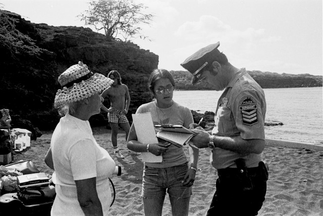 A Department of Defense police officer takes information from Karla Villalba and Ellen Miles. Kimo Aluli is in the background.