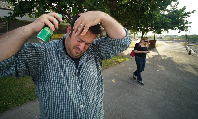 Colleague Engagement Editor Anthony Quintano loads up on the 'Deet' spray while waiting for Civil Defense and other Hawaii county officials to meet media.