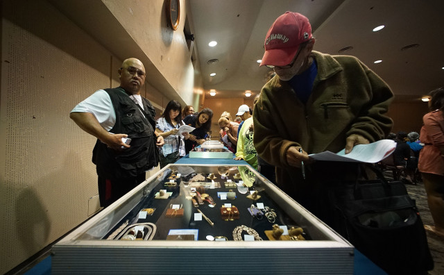Members of the public / potential bidders view some of the jewelry and other valuables in covered containers before the AG offices' auction of forfeited property held at Neal Blaisdell Exhibition Hall. 9 april 2016.