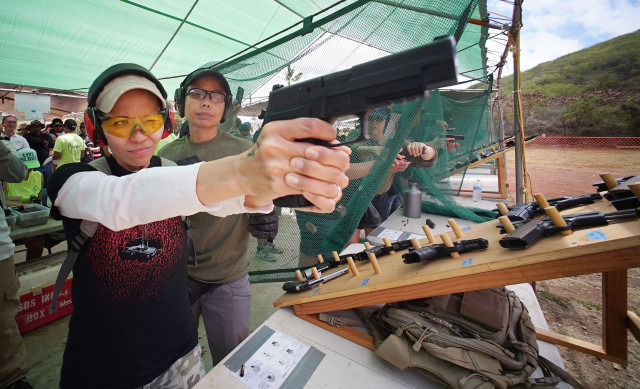 Christy Agena from Kaneohe fires a 9mm Beretta handgun during 23rd Annual Shooting Sports Fair sponsored by the Hawaii Rifle Association at Koko Head shooting complex. 19 june 2016