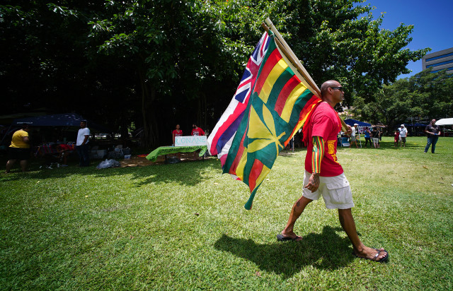 La Hoihoi Ea festival Thomas Square Hawaiian flag day as person strolls through park carrying a pair of flags. 30 july 2016