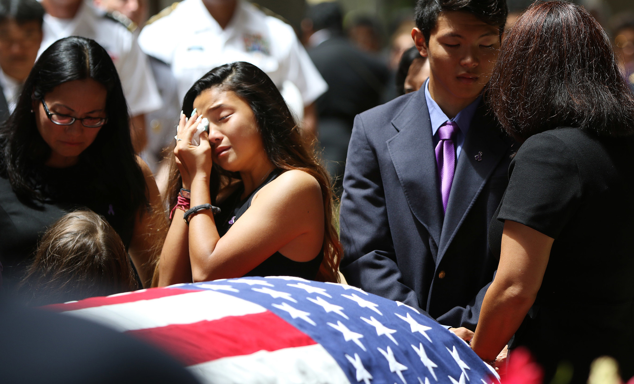 <p>Kaila Takai wipes away tears for her father with her brother, Matthew, at her side.</p>