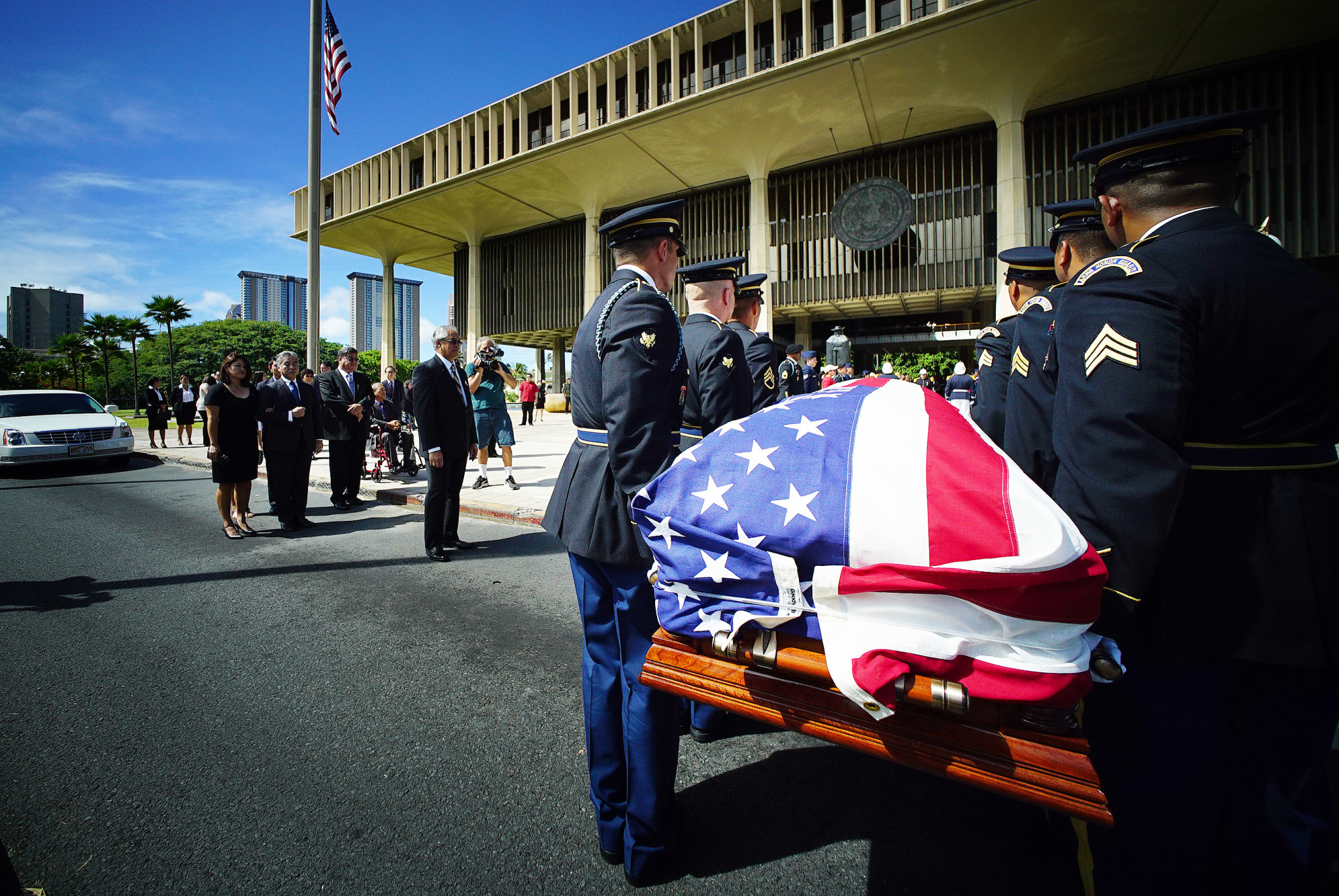 <p>Members of the Honor Guard from the Hawaii National Guard prepare to carry U.S. Rep. Mark Takai's casket into the Hawaii State Capitol, while Gov. David Ige and Takai's widow, Sami, wait.</p>