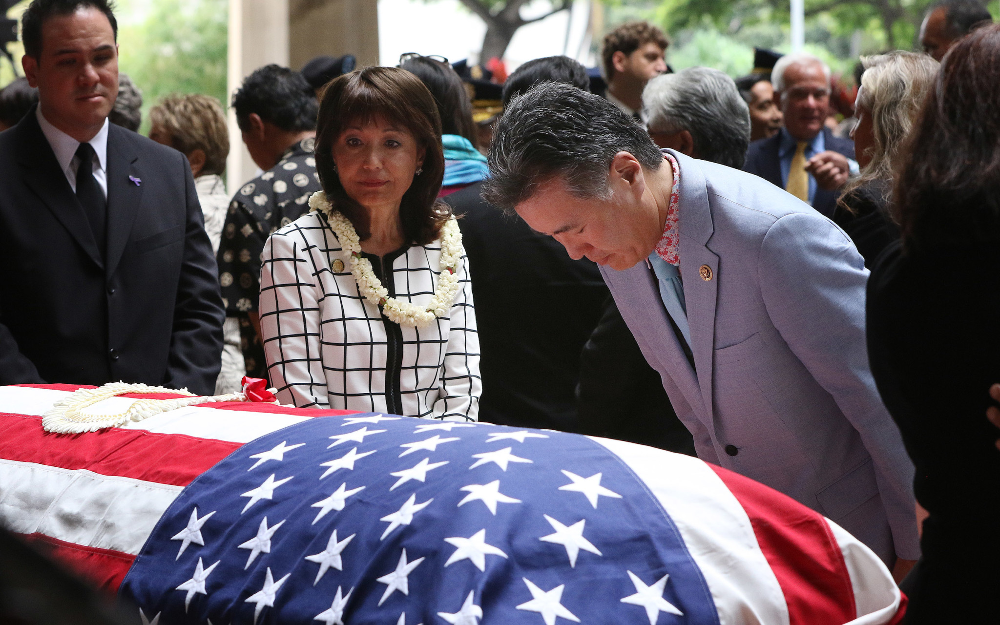 <p>California Congressman Mark Takano bows his head at Takai's casket, as state Sen. Donna Mercado Kim and state Rep. Aaron Ling Johanson wait to pay their respects.</p>