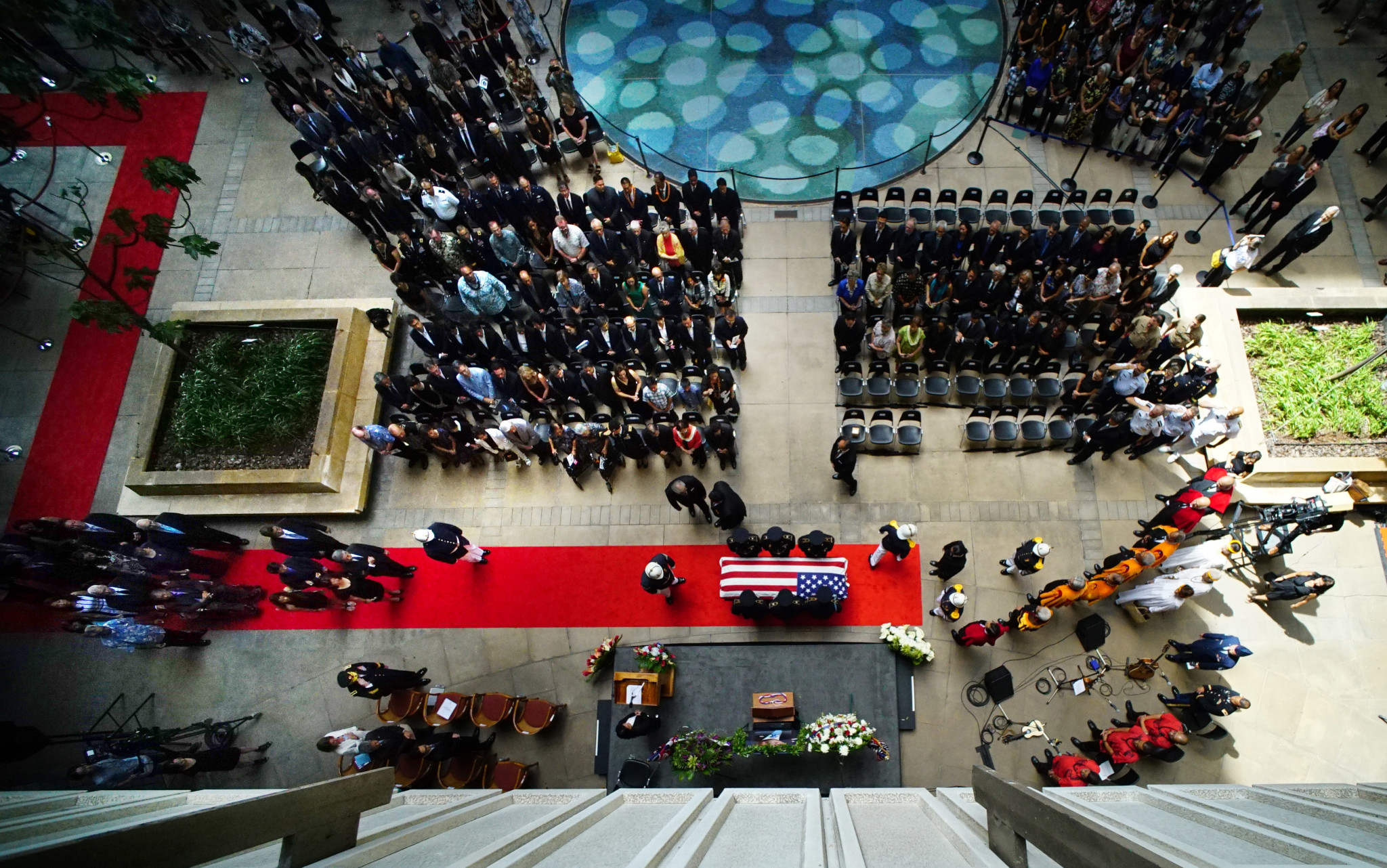 <p>Gov. David Ige and Sami Takai lead a procession of family members into the Capitol Rotunda as the service begins.</p>