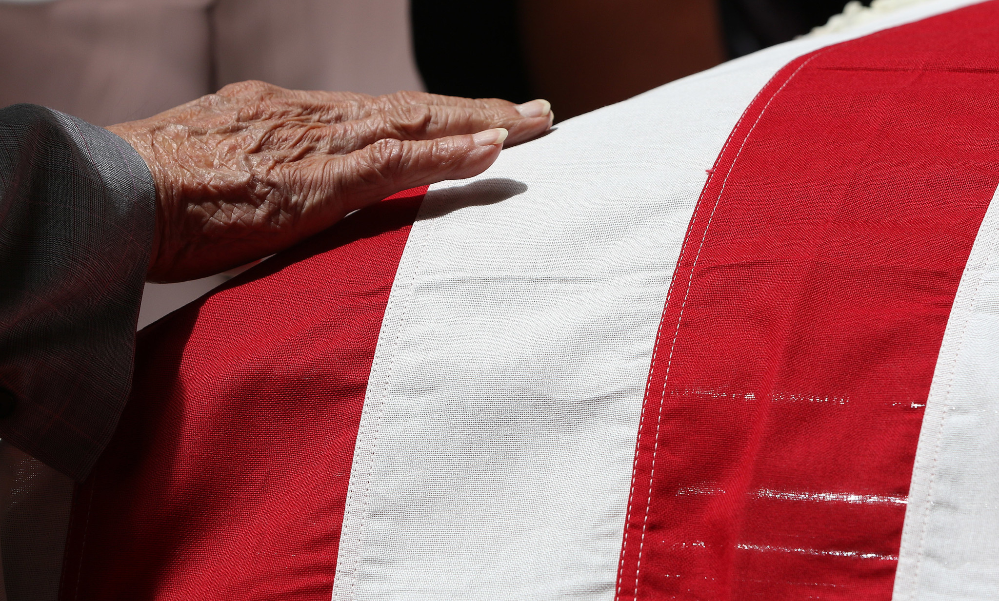 <p>A mourner touches the flag atop Takai's casket in a gentle farewell.</p>