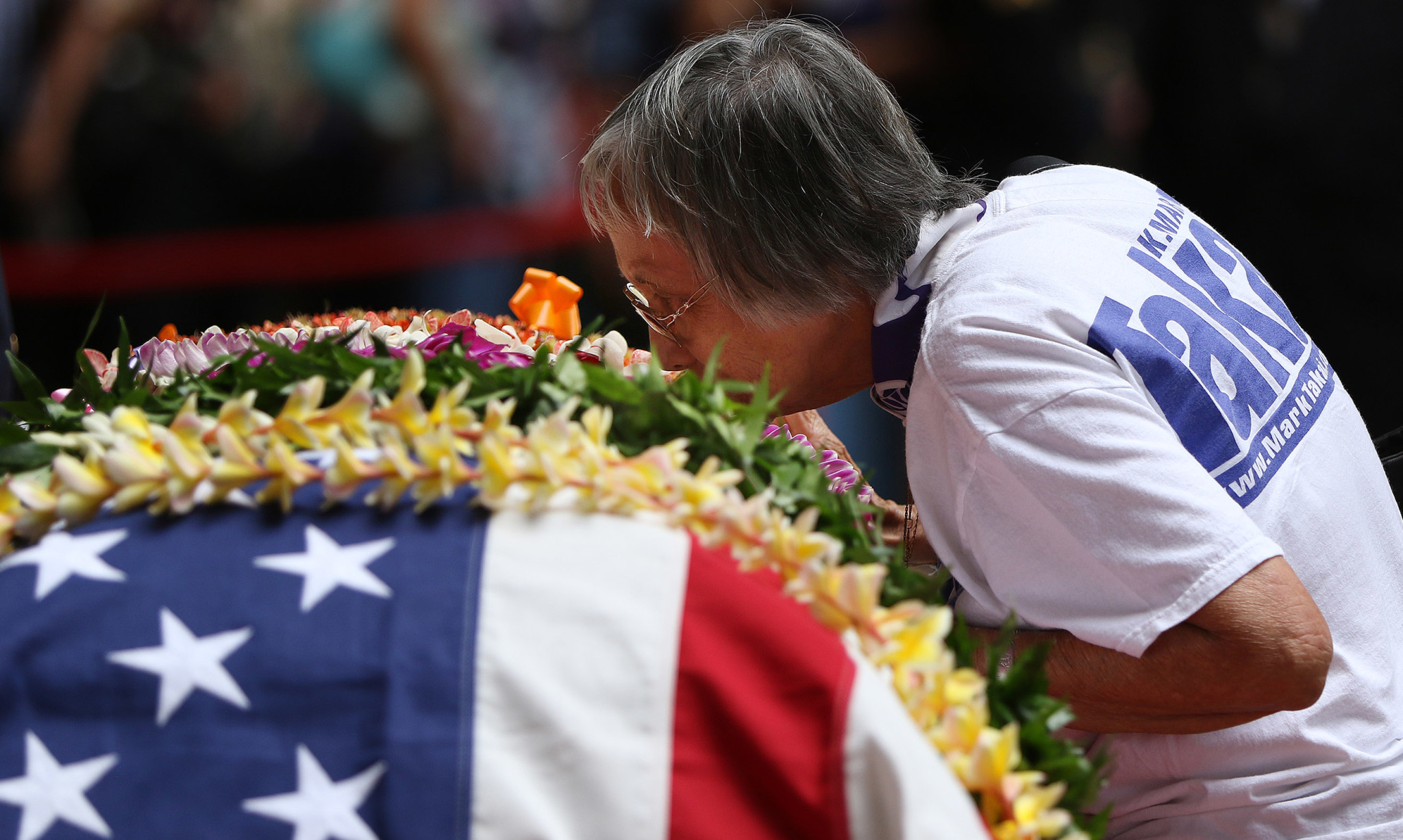 <p>Wearing a Takai campaign shirt, Frances Espiritu kisses Takai's casket as she and other supporters and friends say their goodbyes.</p>